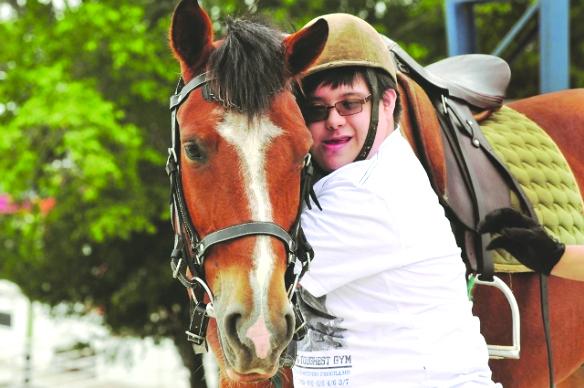 #PraCegoVer Fotografia. Um menino com síndrome de down abraça um cavalo marrom. O menino possui pele branca, usa uma camiseta branca, um óculos de grau e um chapéu equestre. Desfocado, ao fundo, há uma vegetação.