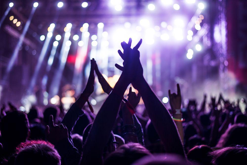 #PraCegoVer Audiodescrição Resumida: Fotografia de um show musical. Nela, há diversas pessoas com os braços para cima. Desfocado, ao fundo, há um palco com holofotes que transmitem luzes roxas.
