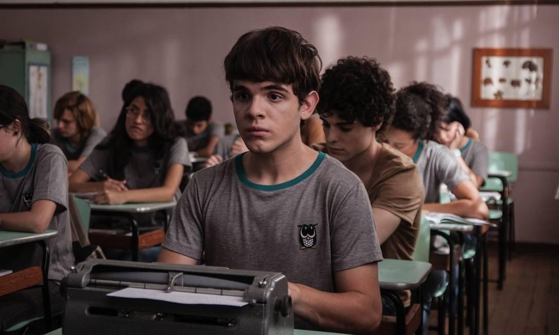 """#PraCegoVer Audiodescrição resumida: Fotografia do filme """"Hoje eu quero voltar sozinho"""". Em uma sala de aula, há meninas e meninos sentados em cadeiras, debruçados sobre mesas enfileiradas. Sentado à frente, há um menino de pele branca, cabelos e olhos castanhos. Ele usa uma camiseta cinza com um pequeno desenho de uma coruja à direita. Em cima de sua mesa há uma máquina de escrever em braile."""