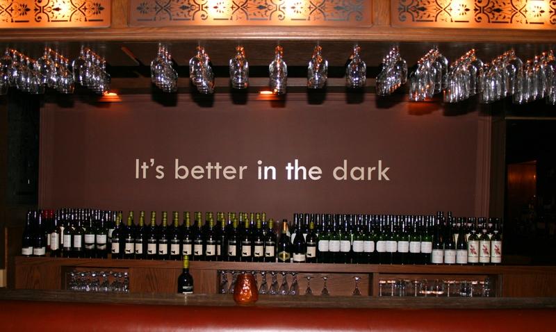 #PraCegoVer Audiodescrição resumida: Fotografia vista de frente de um balcão contendo diversas garrafas de vinho. Acima do balcão há taças de vidro presas de cabeça para baixo. Ao fundo, em uma parede marrom, está o texto: It's better in the dark.