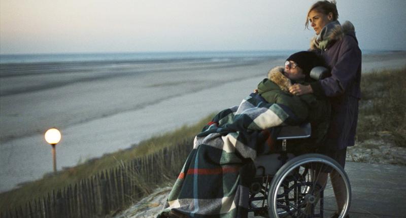 """#PraCegoVer Audiodescrição resumida: Fotografia do filme """"O Escafandro e a Borboleta"""". Em uma praia, uma mulher está em pé atrás de um homem, que está sentado em uma cadeira de rodas. A mulher possui pele branca, cabelos loiros presos e usa roupas de frio. O homem usa um óculos de grau, uma touca e está coberto com uma manta xadrez. Ao fundo há um mar e um céu acinzentado."""
