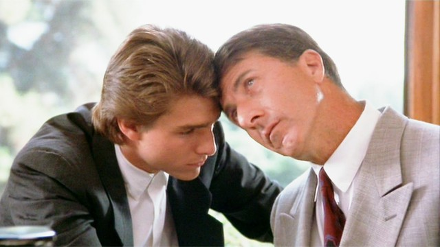 """#PraCegoVer Audiodescrição resumida: Fotografia do filme """"Rain Man"""". No centro, há dois homens sentados com a testa encostada na testa do outro. À esquerda, o homem de pele branca e cabelos loiros; ele usa um terno preto, uma camisa branca e olha para baixo. À direita, o homem de pele branca e cabelos castanhos; ele usa um terno cinza, uma camisa branca, gravata vermelha e olha para cima."""