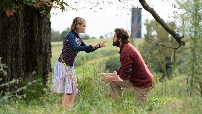 """#PraCegoVer Audiodescrição Resumida. Foto do filme """"Um Lugar Silencioso"""". Em um campo aberto, uma menina e um homem estão frente a frente. Ela faz um sinal com ambas as mãos. O homem está ajoelhado e olha fixamente para a menina."""
