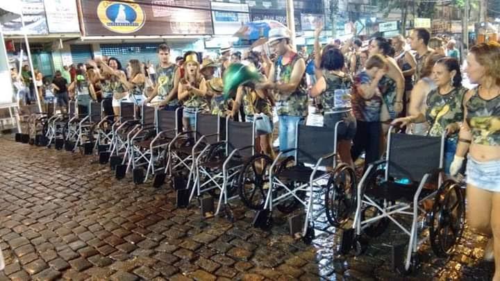 #PraCegoVer Audiodescrição resumida: Fotografia tirada em uma área externa. Em uma calçada de paralelepipedos há diversas pessoas uniformizadas e enfileiradas. À frente da primeira fileira estão postas cadeiras de rodas.