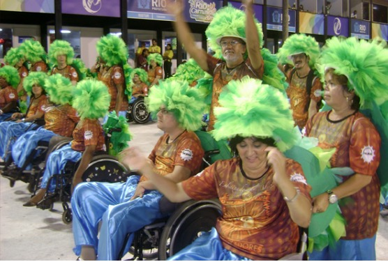 #PraCegoVer Audiodescrição resumida: Fotografia registrada em uma passarela de chão em tons de branco. Ao fundo, na parte superior, à esquerda, localizam-se banners expostos em tons de roxo e amarelo. Ao centro da imagem, pessoas desfilando e locomovendo pessoas deficientes físicas de cadeiras-de-rodas. Todos vestem camisetas em tons alaranjados e calças em tons de azul-claro reluzentes. Em suas cabeças estão perucas em tons de verde e aparentam estar dançando.