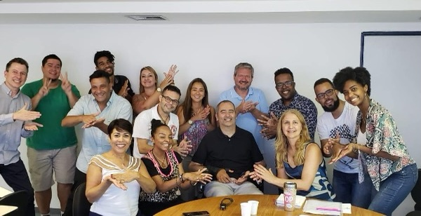#PraCegoVer audiodescrição resumida: Em uma sala branca, quinze integrantes da equipe de tradutores de libras do samba-enredo de São Paulo estão juntas e sorriem para a foto. A maioria faz o mesmo sinal de mão, enquanto outros fazem apenas gestos.