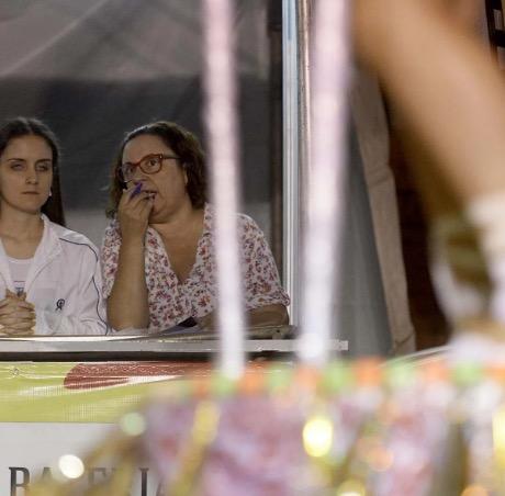 #PraCegoVer audiodescrição resumida: Fotografia de duas mulheres. Ao fundo, em destaque, à esquerda, há uma mulher cega sentada. À direita, há uma mulher de óculos de armação vermelha conversando com ela. Em desfoque, à frente delas, há um objeto brilhante, carregado por cordas brancas.