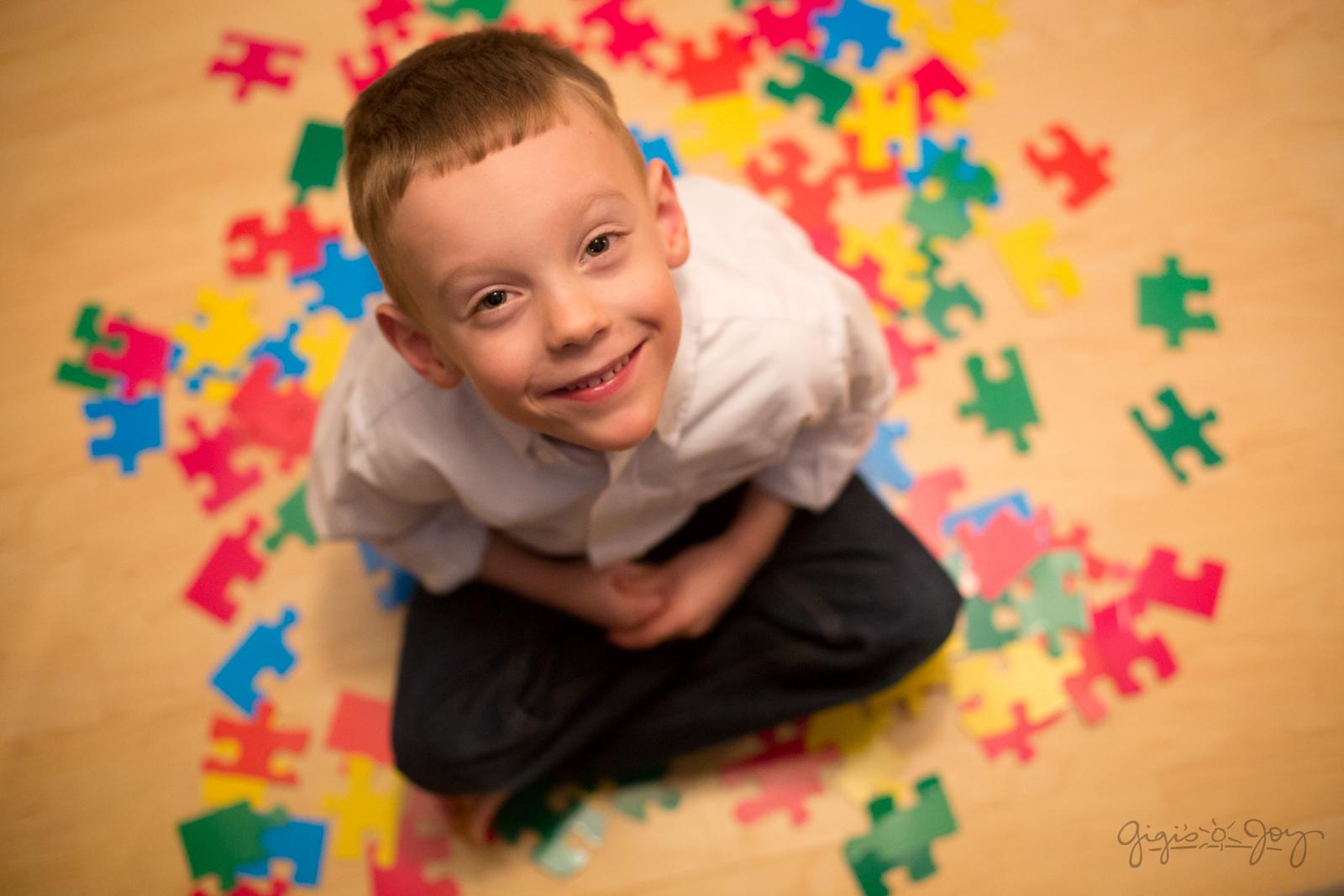 #PraCegoVer Audiodescrição resumida: Fotografia vista de cima. No centro, um menino está sentado no chão com as pernas cruzadas. Ele olha para cima e sorri. No chão, ao redor dele, há várias peças coloridas de quebra-cabeça espalhadas.