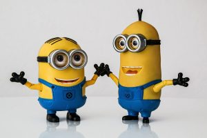 #PraCegoVer Audiodescrição resumida: Fotografia de fundo branco. Ao centro, dois bonecos dos Minions, Stuart e Kevin são bonecos amarelos, de formato alongado e com a cabeça arredondada. Eles usam macacão jeans, óculos redondos prateados, luvas e botas pretas. Eles estão de mãos dadas e sorriem.