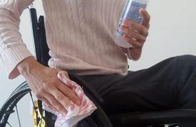 #PraCegoVer Audiodescrição resumida: Imagem do tronco e pernas de uma pessoa sentada em uma cadeira de rodas. A mão esquerda segura um álcool em gel; enquanto a direita, segura um pano em contato com uma das rodas.