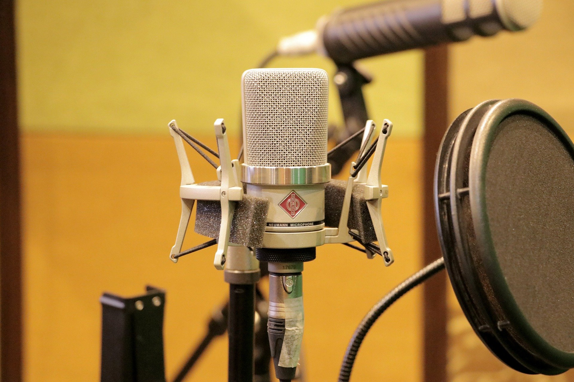 #PraCegoVer Audiodescrição resumida: Fotografia em um estúdio. Ao fundo,parede amarela e um microfone em desfoque . À Frente, a direita, um filtro circular preto de microfone. No centro, um microfone condensador prateado.