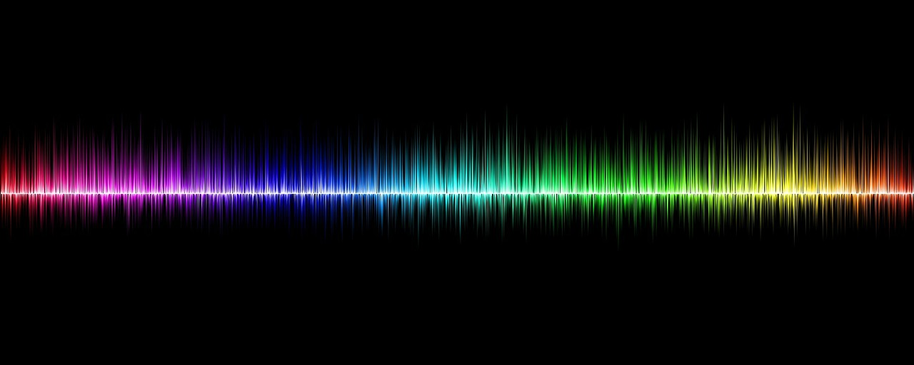 #PraCegoVer Audiodescrição resumida: Imagem retangular com fundo preto. Localizado no centro, há uma representação de uma onda sonora. Nela, da esquerda para direita, estão as cores em degradê: vermelha, rosa, azul, verde, amarela e laranja.