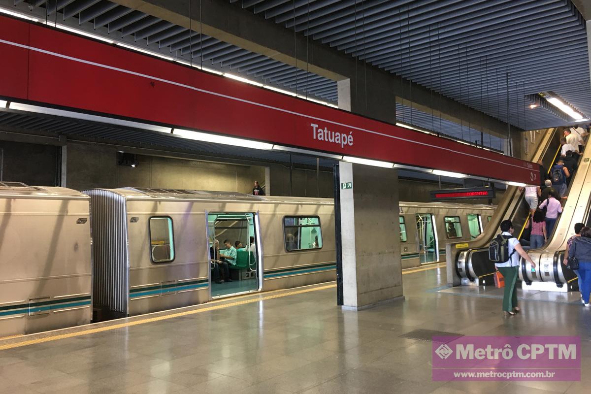 #PraCegoVer Audiodescrição resumida: Fotografia da estação Tatuapé. Ao fundo, há um metrô de portas abertas; à direita do metrô, pessoas sobem uma escada rolante. Sobreposto à imagem, na parte inferior direita, há um retângulo lilás com o texto: Metrô CPTM, www.metroctpm.com.br