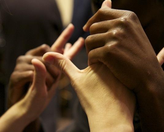 #PraCegoVer audiodescrição resumida: Fotografia. Uma mão de pele negra segura, com os dedos fechados, uma mão de pele branca, que está com a palma aberta. Ao fundo, reflexo desfocado das mãos.